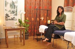 Rita Oosterbeek assise sur la table de massage dans son cabinet. Elle est pieds nus et souri ! Le cabinet est beau, coloré et fleuri !