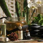 Ustensiles de naturopathie sur une table en bois : thé dans une teillée, plantes, huiles essentielles, huiles végétales, fleurs de back et pierres chaudes.