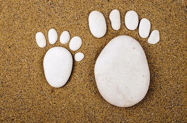 Pierres blanches disposés sur du sable, faisant la forme de deux pieds : un pied d'enfant et un pied d'adulte. Chaque pied est fait d'une grande pierre et cinq petites.