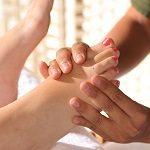 Séance de réflexologie : mains qui massent des pieds sur une table de massage. Les ongles des pieds sont peintes en rouge, mais pas les mais qui massent.
