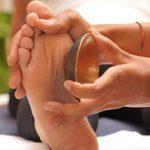 Massage ayurvédique des pieds. Ce massage s'appelle padabhyanga et utilise le bol kansu (bol constitué de cinq métaux) en plus des huiles thérapeutiques.
