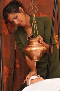 Séance de shirodhara. Il s'agit d'une technique ayurvédique pour relaxer le système nerveux central où on fait couler en continu des huiles chaudes aux plantes médicinales sur le front.